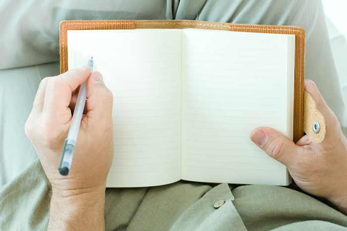 Человек записывает в блокнот